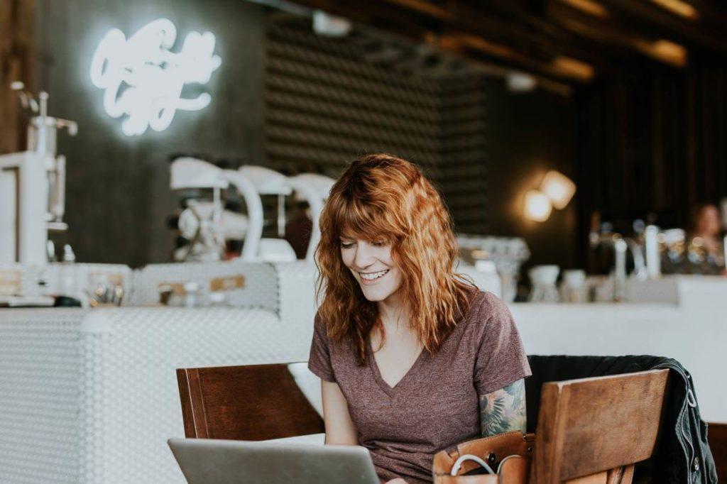 Junge Frau in einem Café an einem Laptop.